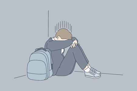 Despair, frustration, depression, mental stress, bullying concept. Young desperate frustrated depressed child schoolboy sitting in corner crying. Negative emotions headache or migraine and bad news.