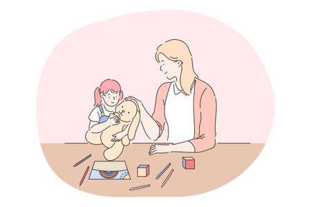 Happy leisure and activities at home with children concept. Young woman mother cartoon character playing, drawing and feeding toy together with her small daughter at home. Relax, rest, family