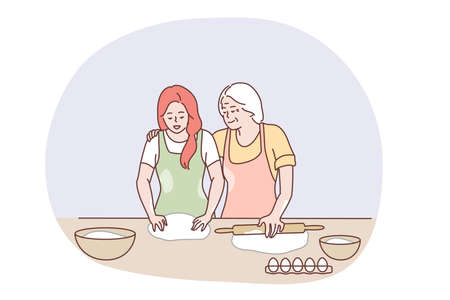 Happy family cooking together concept. Happy elderly grandmother hugging granddaughter and showing how to bake pastry or pie with eggs and dough in kitchen. Baking, family, grandparents help