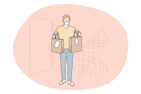 Contactless delivery, courier, online order concept. Young man courier deliveryman in protective medical mask gloves delivering food in paper bags to customer home. Parcel, logistics during pandemic