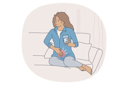 Menstruation pain concept. Young stressed female sitting on bed with glass of water, touching belly and suffering from pain of menses periods at home. Gynecology calendar and pms symptoms