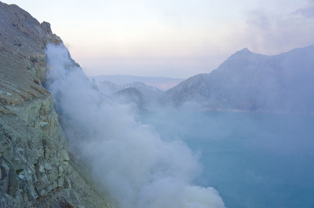 spewing: Ijen volcano in East Java contains the worlds largest acidic volcanic crater lake, called Kawah Ijen, spewing out sulphur smoke in the morning. Sun is hidden in mist.