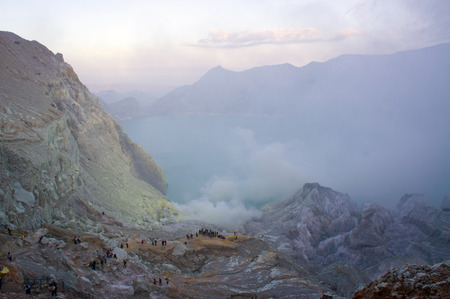 acidic: Ijen volcano in East Java contains the worlds largest acidic volcanic crater lake, called Kawah Ijen, spewing out sulphur smoke in the morning. Sun is hidden in mist.