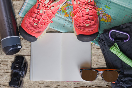 Top view of travel accessories for a mountain trip on old wooden background : hiking boots, pants, camera, bottle, rope, map, notebook and sunglasses.