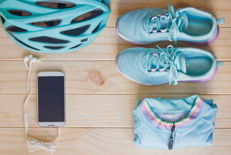 sport clothes: Top view of sport equipment in pastel colour: helmet, shoes, biking clothes, biking gloves, socks, and notebook on wooden background