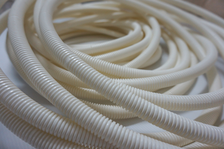 Close up of white flexible conduit equipment for electrical communications or for fiber optic cable
