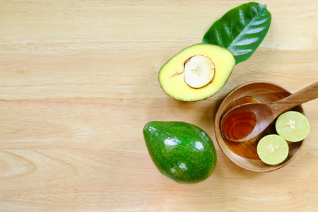 Fresh avocado fruits on a wood background.