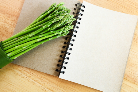 Fresh asparagus on wooden background and blank diary book. Standard-Bild