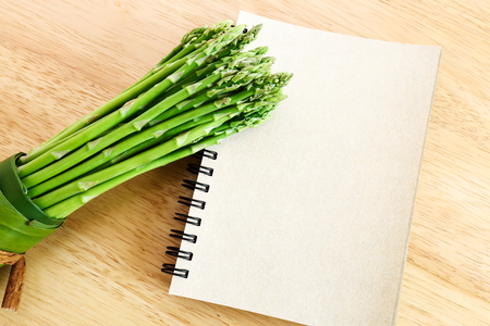 Bundle of fresh asparagus on wooden background and blank diary book.