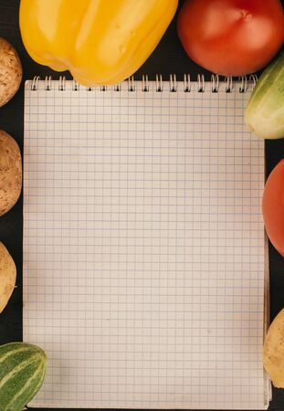 Shopping list, recipe book, diet plan. Fresh raw vegetables, fruit and ingredients for cooking.