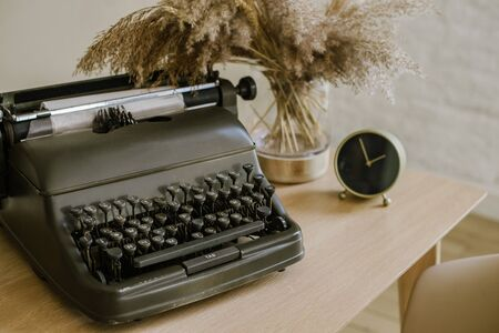 Antique typewriter on a wooden table background with papers ready for a new book or a novel with many failing pages lined up on a desktop. office equipment. clock, pencil Stockfoto