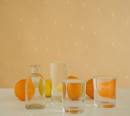 Oranges behind glass vessels filled with water. Distorted reflection 免版税图像