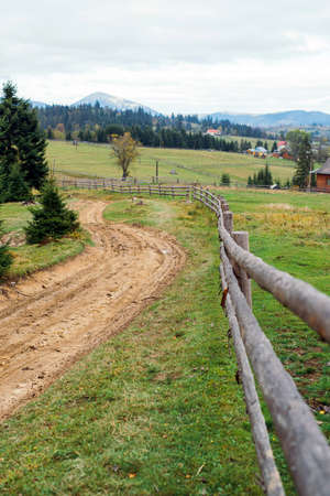 View of a wooden fence in the Carpathians and the path leading to the top. Summer Ukrainian landscape. Wildlife with forest in the hills