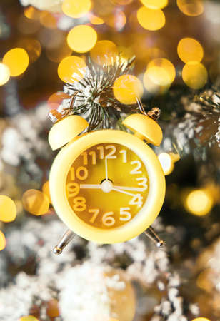 Close-up of a yellow clock showing the countdown to twelve oclock hangs on the Christmas tree next to the glowing golden lights on the background of New Years decor. Merry Christmas