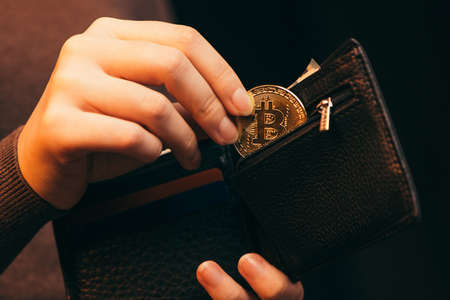 Woman putting golden bitcoin into her wallet on light background, closeup Stock Photo