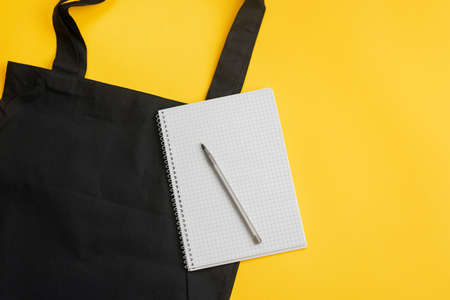 Grocery list in paper notepad, cotton eco black shopping bag on yellow background with copy space, top view. Concept purchases product, horizontal