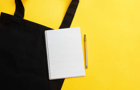 Grocery list in paper notepad, cotton eco black shopping bag on yellow background with copy space, top view. Concept online purchases product, zero waste