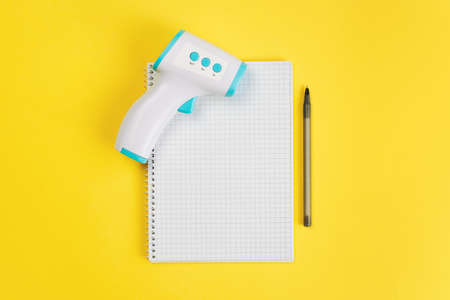 Thermometer and pen with blank paper sheet for list or prescription. Cold and flu time. Yellow background. top view. Empty place for text.