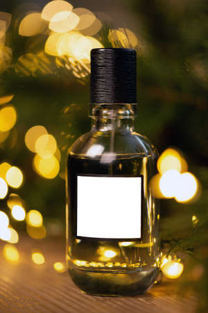 Beautiful composition of a bottle of perfume on a wooden table against the background of garland lights and branches of a Christmas tree. New year gift, holiday concept. Mock up 免版税图像
