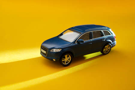 Blue toy off-road vehicle on a yellow background with long sun shadows. Copy space. Delivery, taxi and vacation concept. 免版税图像