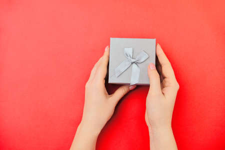 Gentle hands are holding a small gift box on a red background. view from above. holiday concept, giving a gift. valentines day or womens day.
