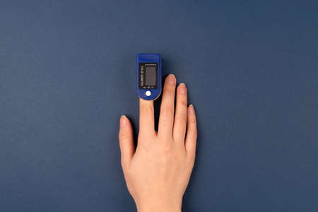 Hand with a finger in pulse oximeter on dark blue background. Self monitoring and protection during pandemic concept. Copy space. TOP view.