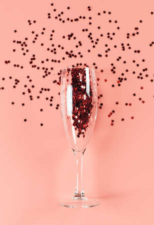 A glass of champagne filled with stars confetti on a pink pastel background. Top view. card blank. Copy space and vertical orientation 免版税图像