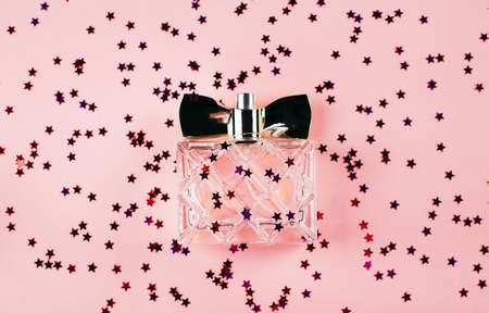 A bottle of women's perfume on a festive pink background with multi-colored sparkles and confetti. view from above. holiday concept february 14 or march 8.