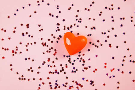 decorative volumetric heart on a pink background with confetti and sparkles. view from above. concept of the holiday of all lovers. Valentine's Day.