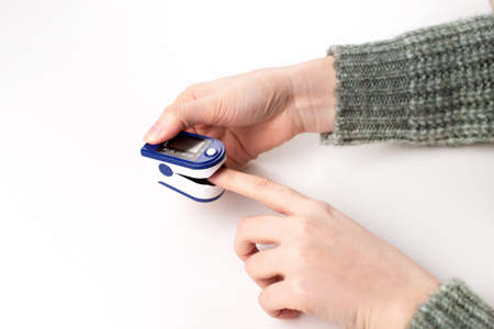 Woman using fingertip pulse oximeter on white background, close up.