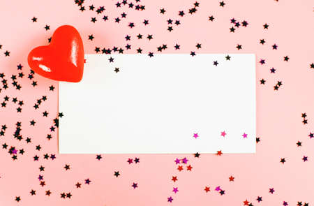 Confetti stars on a pink background with a postcard and copy space. Red decorative heart. The flat lay with space for text. Valentines day concept.