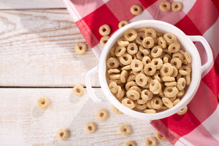 healthy cereal rings on a light wood background with tablecloth red in a plate and scattered on the table with sun rays. morning eat. Healthy children's breakfast. Dry muesli 免版税图像