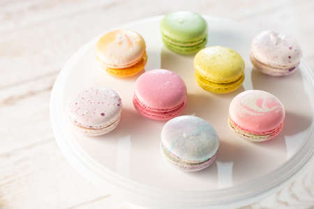 Multi-colored macaroons illuminated by sun rays casting their shadow, on light wood background, selective focus.