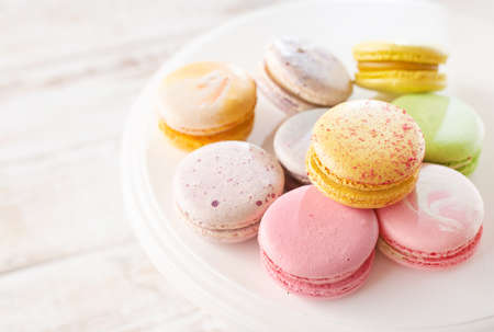 Multi-colored macarons on wood background with soft lights and shadows. Gentle macaroons on table on light background. 免版税图像