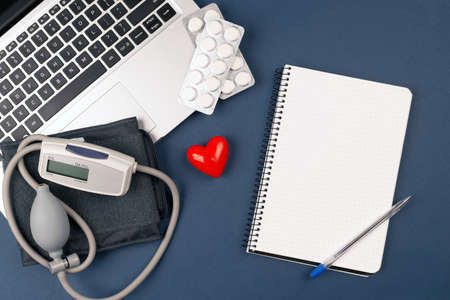 blood pressure meter on laptop with red heart, and pills on dark blue background.paper nootebook with copy space cardiology concept.Tonometer or sphygmomanometer. at the doctor's appointment. 免版税图像