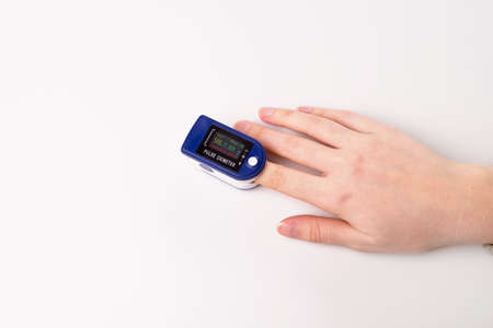 Close up of Finger and hand in an Oximeter Device. Pulse oximeter on white background. top view.