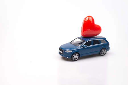 Valentine's Day. Small blue suv toy car with heart on the roof on white background. World Women's Day present delivery. Sale concept. Copy space 免版税图像