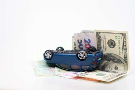 Blue suv toy car accident in overturned composition on money cash on white background. Saving, Financial, Installment payment and accident transport concept. Car crash insurance and lose money
