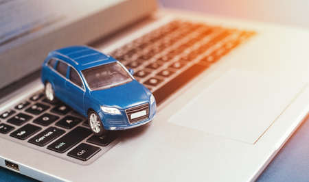Symbol of online auction, insurance and sale car. Blue toy suv car and laptop. car business concept such as transportation, rental, sell and buy.