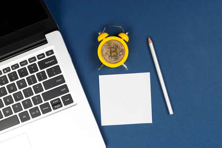 Concept deadline for cryptocurrency investment showing alarm clock with bitcoin as clock face on blue background and laptop with sticker. Time to invest in the Bitcoin idea.