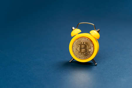 Concept deadline to invest in cryptocurrency showing alarm clock with a bitcoin as the clock face on blue background. Time to invest in bitcoin idea