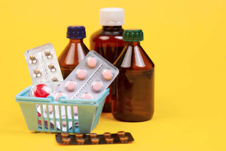 A bunch of pills in a grocery basket on a yellow background. Pharmacies make a profit. Medications for covid. Remedy for colds and flu Tablets, bottles