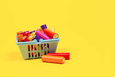 Used batteries in a supermarket basket on a yellow background. The concept of recycling of batteries. grocery basket. Recycling concept. Save environment.