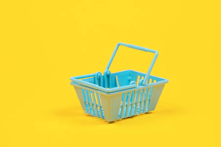 Toy plastic shopping basket on a yellow background with copy space. basket for grocery 免版税图像