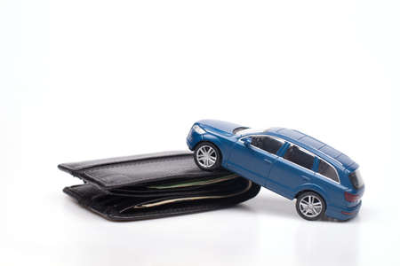Close-up conceptual image of a blue toy car on a black wallet representing car loans, debts and related expenses. credit and insurance. On white background