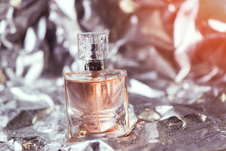 Stylish bottle of women perfume on the foil with shiny crumpled surface silver background with water drops. selective focus 免版税图像