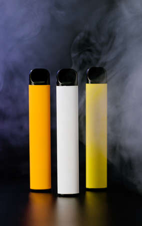 Colorful disposable electronic cigarettes on a black background with smoke. The concept of smoking, vaping and nicotine. 免版税图像