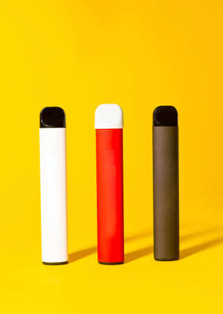 Colorful disposable electronic cigarettes with shadows on a yellow background. The concept of modern smoking, vaping and nicotine