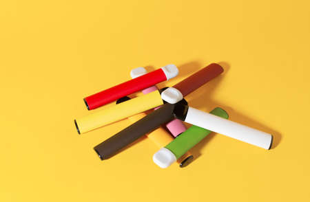 Layout of colorful disposable electronic cigarettes with shadows on a yellow background. The concept of modern smoking, vaping and nicotine. Top view.