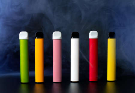 Set of colorful disposable electronic cigarettes on a black background with smoke. The concept of modern smoking, vaping and nicotine
